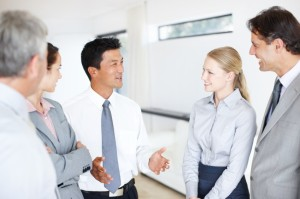A group of businesspeople talking to one another in an informal meeting